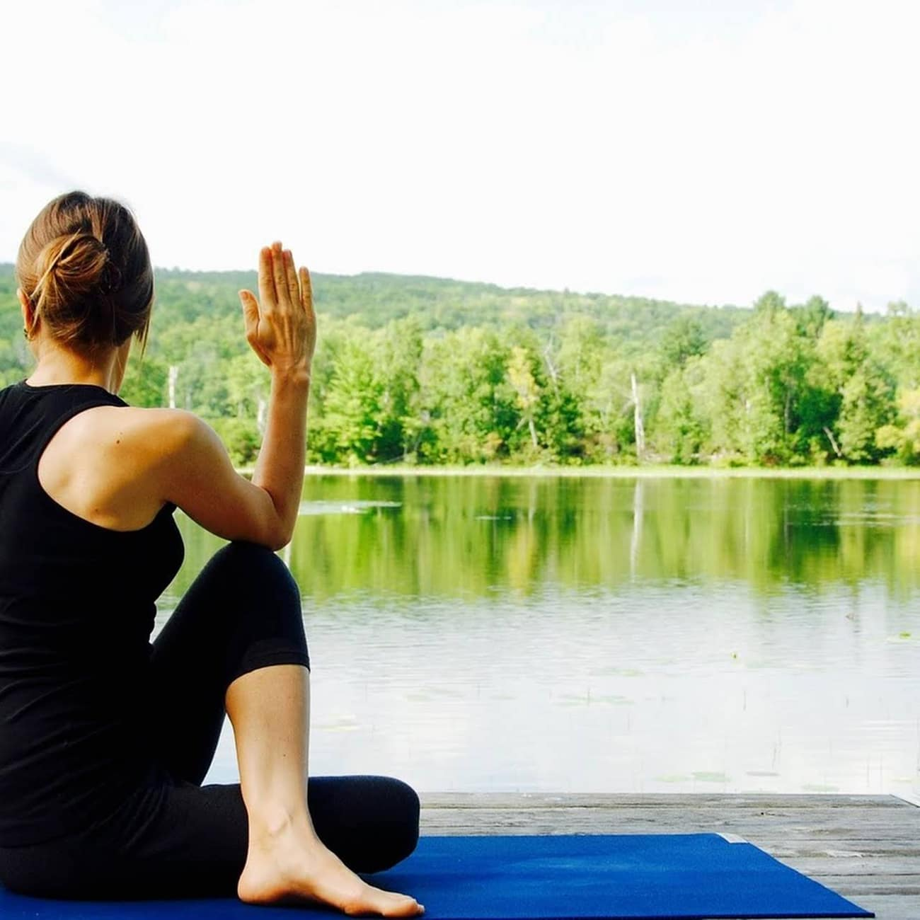 Woman doing yoga pose on a yoga mat outside by the lake for healthy 2020 year